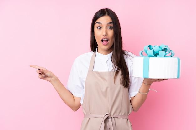 側に驚くと人差し指で大きなケーキを持つ若い女性