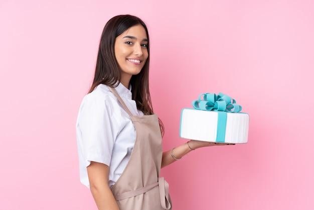 たくさんの笑顔で大きなケーキを持つ若い女性