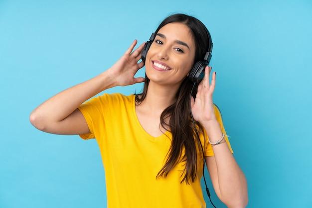 青いリスニング音楽上の若いブルネットの女性