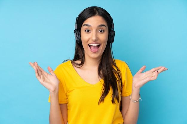 Молодая брюнетка женщина над синим сюрпризом и прослушивания музыки