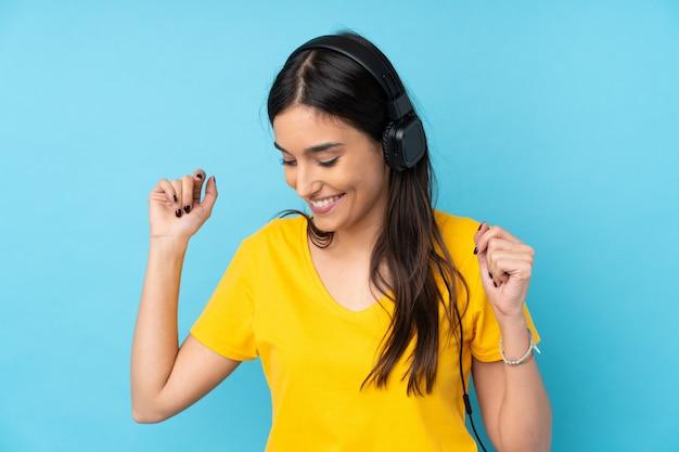 青い音楽を聴くと踊りの上の若いブルネットの女性