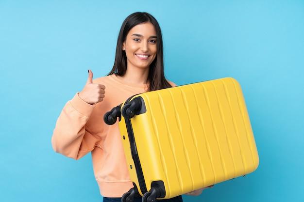 旅行スーツケースと親指アップと休暇で青の上の若いブルネットの女性