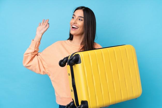 旅行スーツケースと敬礼と休暇で青の上の若いブルネットの女性