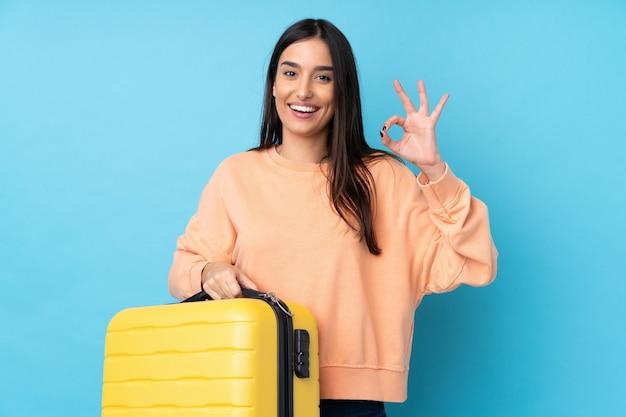 Молодая брюнетка женщина над синим в отпуске с чемоданом путешествия и шляпу