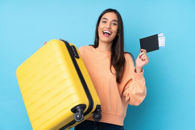Молодая брюнетка женщина над синим в отпуске с чемоданом и паспортом