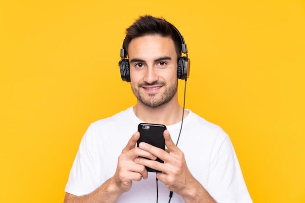 黄色の携帯電話で音楽を聴くと正面を探している若い男