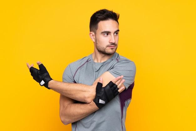 Спортивный человек над желтой стеной протягивая руку