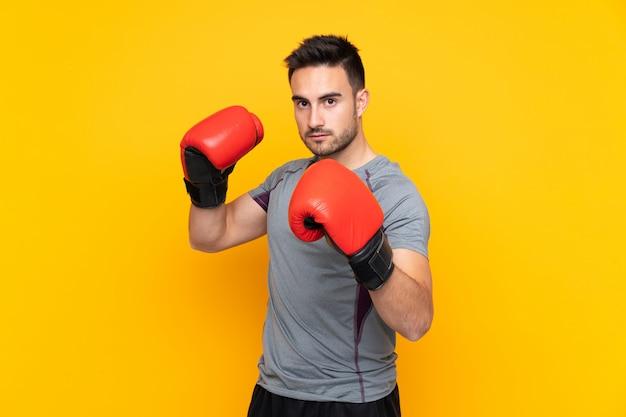 Спортивный человек над желтой стеной с боксерскими перчатками