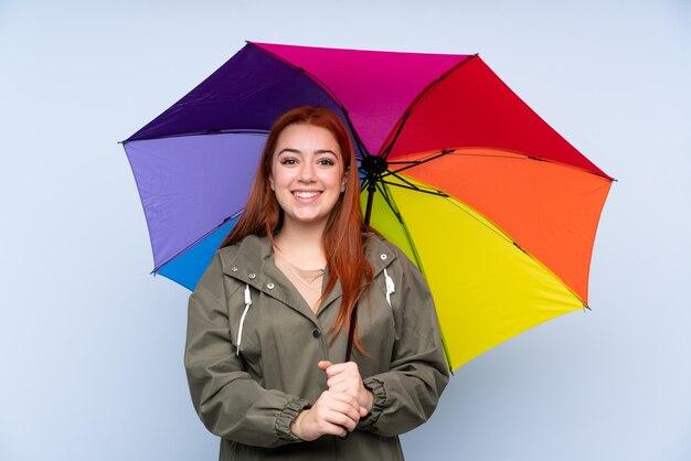 Рыжая девушка-подросток держит зонтик над синим с удивленным выражением лица