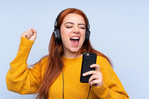 青の携帯電話と歌で音楽を聴く上の赤毛のティーンエイジャーの女の子