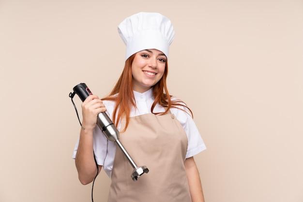 Рыжая девушка-подросток с помощью ручного блендера над улыбкой много