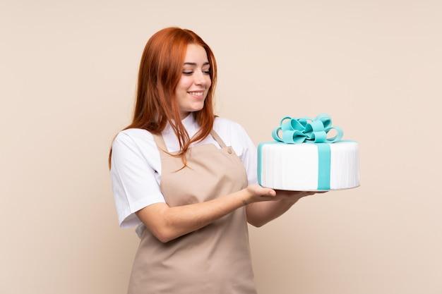 幸せな表情で大きなケーキと赤毛のティーンエイジャーの女の子