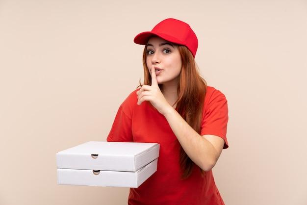 沈黙ジェスチャーをしてピザを保持しているピザ配達ティーンエイジャーの女の子