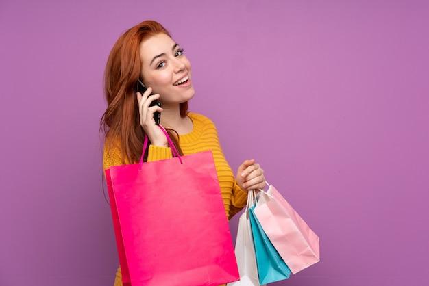 Рыжая девушка-подросток на фиолетовом фоне держит сумки и звонит другу со своего мобильного телефона