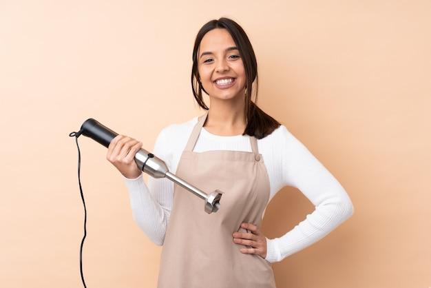 Молодая брюнетка девушка, используя ручной блендер, позирует с руки на бедра и улыбается