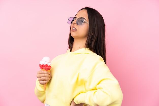 ピンクの背中の痛みに苦しんでいるコルネットアイスクリームを保持している若いブルネットの少女