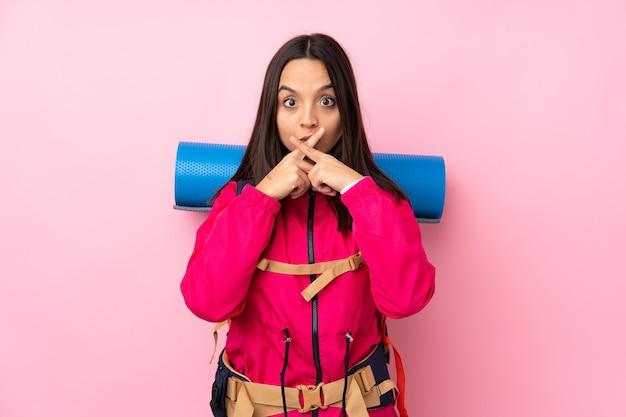 Молодая девушка-альпинистка с большим рюкзаком на розовом фоне с жестом молчания