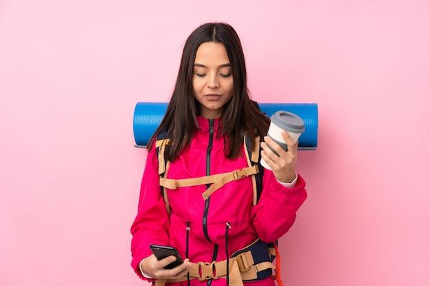 持ち帰るコーヒーと携帯電話を保持しているピンクの上の大きなバックパックを持つ登山少女
