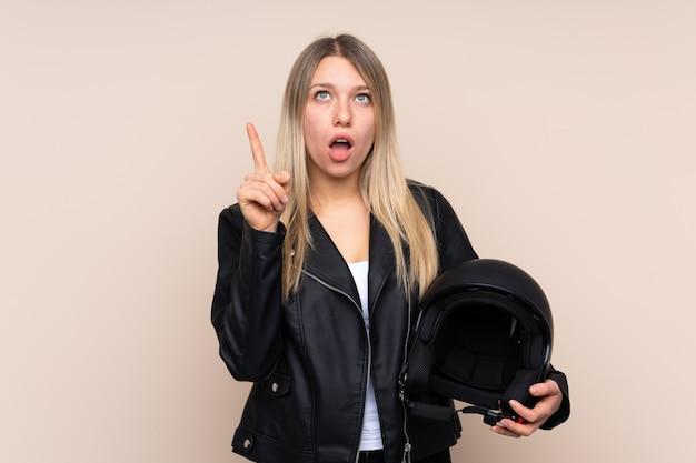 人差し指で素晴らしいアイデアを指す上のオートバイのヘルメットを持つ若いブロンドの女性