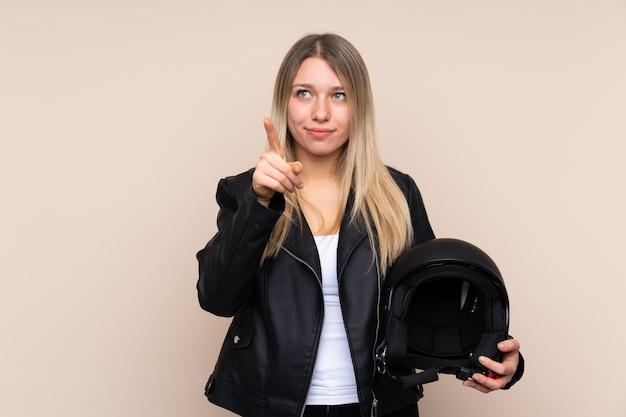 透明なスクリーンに触れる上のオートバイのヘルメットを持つ若いブロンドの女性