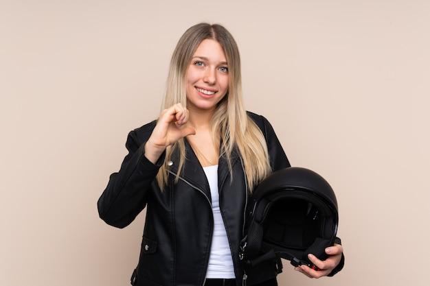誇りと自己満足の上のオートバイのヘルメットを持つ若いブロンドの女性