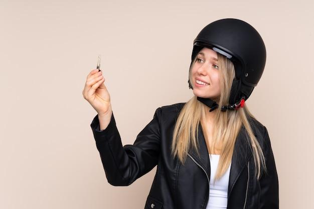 オートバイのヘルメットを持つ若いブロンドの女性