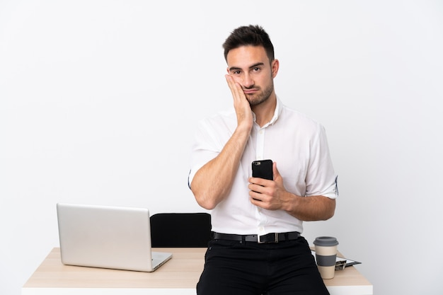 不幸でイライラした職場で携帯電話を持つ若いビジネスマン