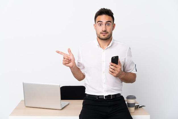 Молодой деловой человек с мобильным телефоном на рабочем месте, указывая на боковые стороны, имеющие сомнения