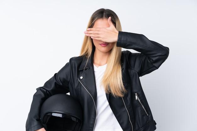 Молодая уругвайская женщина с мотоциклетным шлемом на белом фоне покрывает глаза руками