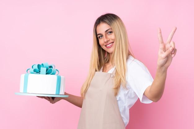笑みを浮かべて、勝利のサインを示す分離のピンクの壁に大きなケーキを持つ若いウルグアイ菓子女性