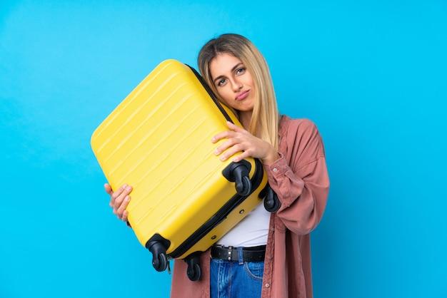 Молодая уругвайская женщина над синей стеной в отпуске с чемоданом путешествия и несчастной