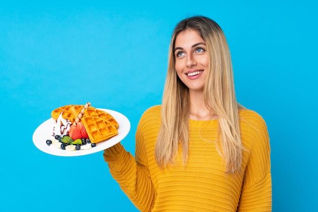 Молодая женщина, держащая вафли на изолированной стене, глядя вверх во время улыбки