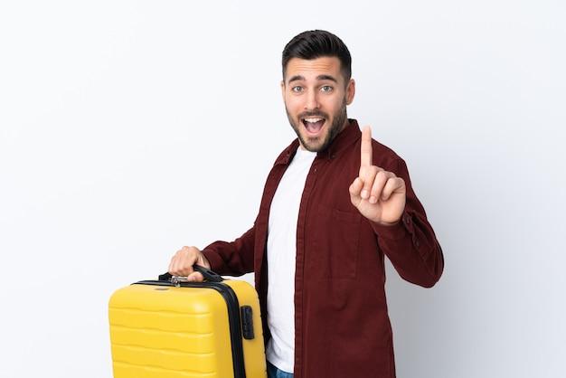 Молодой красавец над изолированной белой стеной в отпуск с чемоданом путешествия и подсчета один