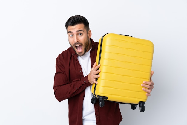旅行スーツケースと休暇で孤立した白い壁の上の若いハンサムな男と驚いた