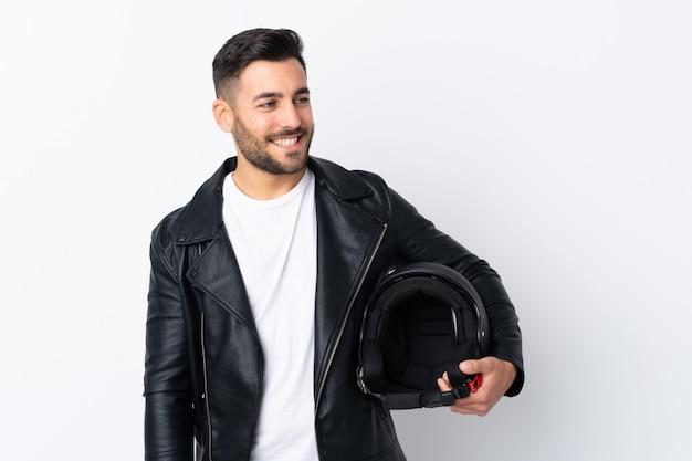 笑っているオートバイのヘルメットを持つ男