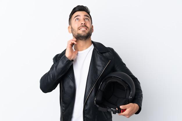 アイデアを考えてオートバイのヘルメットを持つ男