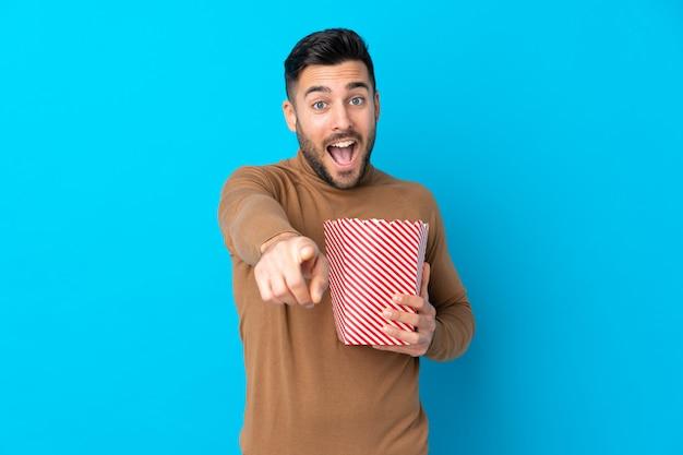 Молодой красивый мужчина держит большое ведро попкорна, указывая спереди