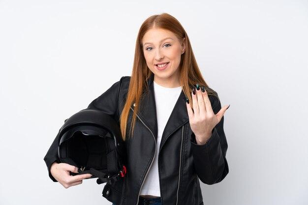 手で来ることを招待して孤立した白い壁にオートバイのヘルメットを持つ若い赤毛の女性。