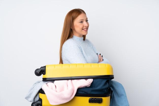 側にいる服でいっぱいのスーツケースを持つ旅行者女性
