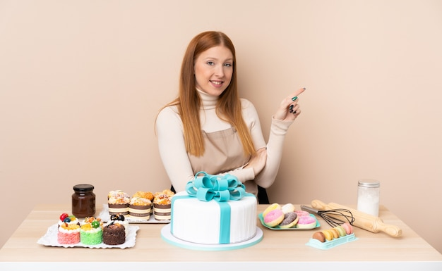 側に指を指している大きなケーキを持つ若い赤毛の女性