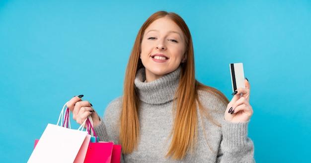 買い物袋とクレジットカードを保持している分離の青い壁の上の若い赤毛の女性
