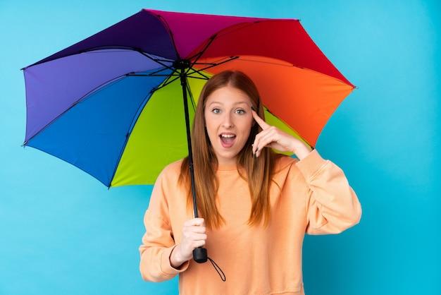 解決策を実現するつもりの孤立した壁に傘を保持している若い赤毛の女性