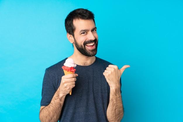 Молодой человек с мороженым корнет над синей стеной с недурно жест и улыбается