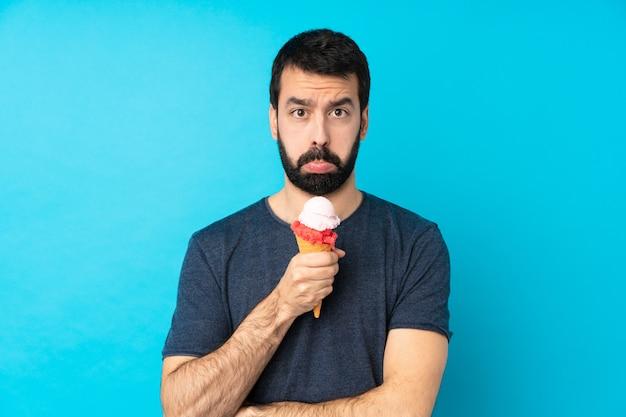 悲しいと落ち込んだ表情で孤立した青い壁の上のコルネットアイスクリームと若い男