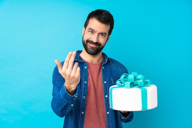 手で来ることを誘って分離の青い壁の上の大きなケーキで若いハンサムな男。あなたが来て幸せ