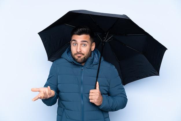 Человек, держащий зонтик над изолированной стеной, делая сомнения жест, поднимая плечи