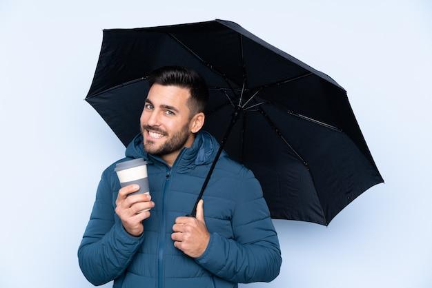 Мужчина держит зонтик над изолированной стеной