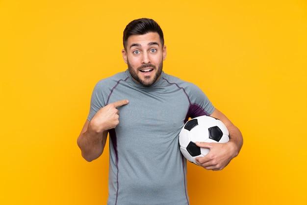 Футболист человек над изолированной стеной с удивленным выражением лица