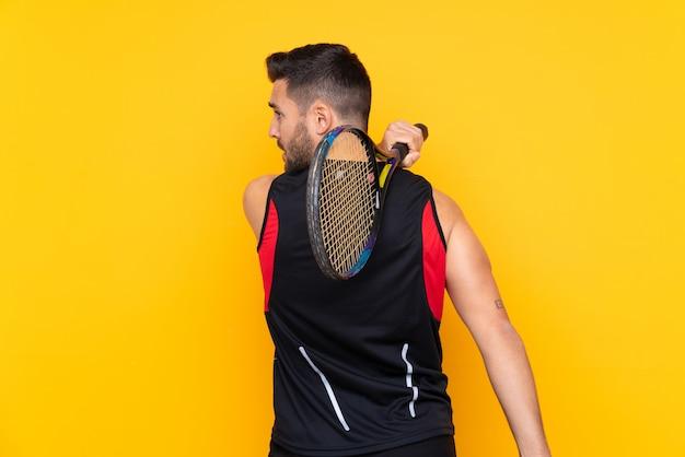 Человек над изолированной желтой стеной, играя в теннис