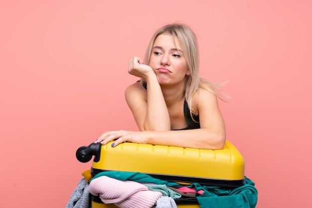 孤立したピンクの壁の上の服でいっぱいのスーツケースを持つ旅行者女性